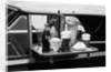Food tray with soda fountain items on car window at 1950s style drive-in restaurant by Corbis