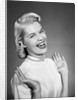 Woman wearing pearls smiling with hands up thumbs tucked under arm by Corbis