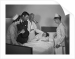 Man doctor woman nurse mother father seeing visiting smiling little girl patient in hospital bed by Corbis