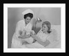 Woman nurse giving baby to smiling mother patient sitting in hospital bed by Corbis