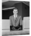 Smiling man bank teller savings accounts sign on counter by Corbis