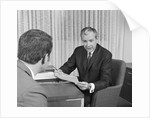 Man from behind meeting at desk of older businessman by Corbis