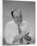 Balding businessman wearing eyeglasses shirt sleeves smiling writing notepad by Corbis