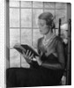 Elegant woman wearing pearls sitting by window reading book by Corbis