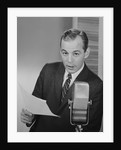 Serious man speaking into microphone holding papers newsman announcer broadcaster by Corbis