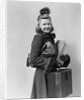 Smiling young blond woman wearing hat fur trimmed coat carrying packages by Corbis