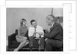 Couple sitting on couch talking to salesman by Corbis