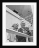 Smiling mature couple at shipboard rail with binoculars by Corbis
