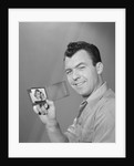 Smiling man holding up wallet with picture of wife and daughter by Corbis
