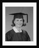 Portrait smiling young woman wearing graduation cap and gown by Corbis