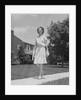 Woman wearing print dress holding handbag walking down suburban street by Corbis