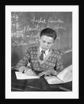 Boy vee neck sweater writing at school desk by Corbis