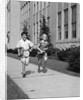 Boy girl running down sidewalk carrying school books smiling by Corbis