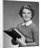 Adolescent teen girl smiling portrait holding school books by Corbis