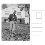 Smiling man raking autumn leaves in front yard of house by Corbis