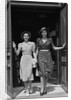 Two smiling women walking out doorway of a store by Corbis