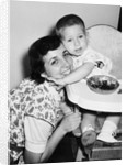 Baby boy hugging mother at dinner time, ca. 1953 by Corbis