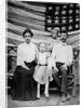 Family pose in front of American Flag, ca. 1898 by Corbis