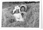 A young brother and sister nestled in the hay, ca. 1900. by Corbis