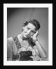 1950s housewife woman in print apron hand up to temple headache pain sad depressed facial expression worried serious looking at camera by Corbis