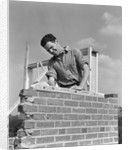 1940s man working with level on brick wall chimney construction by Corbis