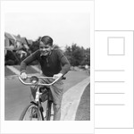 1930s smiling boy riding bicycle by Corbis