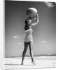 1960s woman in stripes swim suit bathing holding beach ball standing on tip toes by Corbis