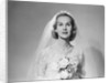 1950s portrait of woman bride wearing white wedding dress veil string of pearls holding a bouquet of flowers looking at camera by Corbis