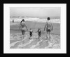 1970s family on vacation at ocean beach holding hands walking on sand in surf by Corbis