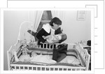 1980s working mother standing over crib holding one baby while other sleeps briefcase in crib indoor by Corbis