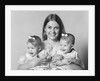 1970s portrait of smiling mother with arms around twin girls with bows in hair looking at camera by Corbis