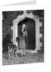 1920s fashionable smiling woman wearing cloche hat coat with fur trim and german shepherd dog on leash standing in arched doorway by Corbis