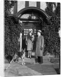 1920s couple wearing coat hat gloves on steps ivy covered building with german shepherd dog on a leash by Corbis