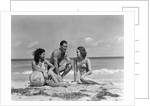 1930s 1940s two women one man in bathing suits sitting on beach by Corbis