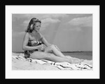1950s woman in strapless one-piece bathing suit seated on beach towel putting on suntan lotion by Corbis