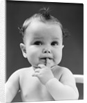 1940s thoughtful baby with finger in mouth by Corbis