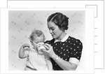 1930s woman mother giving baby daughter drink from mug by Corbis