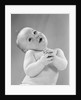 1950s baby in diaper head to one side arms hands clasped in front by Corbis