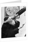 1930s old astronomer white hair and beard wearing skull cap looking through telescope by Corbis