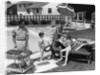 1960s family of 4 in backyard at poolside father barbecuing & mother & children making preparations at picnic table by Corbis