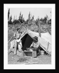 1930s smiling talking couple working by rustic western campsite tent man in cowboy hat smoking pipe washing skillet woman drying dishes by Corbis