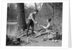 1920s 1930s man & woman camping by lake having picnic woman sitting man standing serving food to woman east creek swamp by Corbis