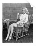 1940s blonde woman in bamboo chair holding up glass of milk smiling wearing white shorts looking at camera by Corbis