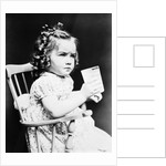 1930s child girl sitting in high chair holding glass of milk serious look bow in hair baloney curls by Corbis