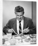 1950s smiling man in suit and tie sitting at table holding knife and fork eating dinner by Corbis