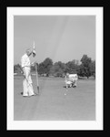 1930s 1940s elderly men on golf green one holding flag the other kneels lining up his putt by Corbis