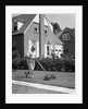 1940s 1950s elderly overweight man pushing lawn mower in front of brick house by Corbis