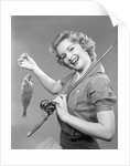 1950s smiling woman with a fishing rod over her shoulder holding up a fish looking at camera by Corbis