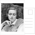 1930s portrait of woman looking down with sad expression and her chin resting on index finger by Corbis