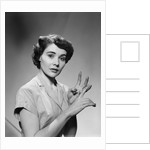 1950s serious woman counting on hands by Corbis